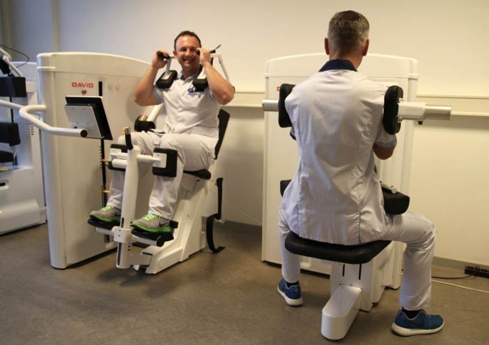 De artsen van campus Henri Serruys laten patiënten oefeningen doen en meten daarbij de kracht van hun buikspieren en van hun rugspieren.