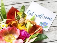 Een ruiker bloemen op een houten ondergrond met een kaart met opschrift Get well soon