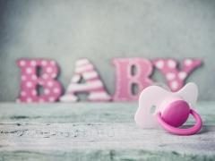 Kaart met wit en roze fopspeen. Het woord baby op de achtergrond in roze letters
