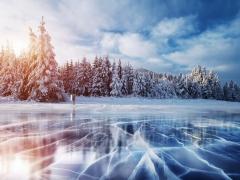 Zonnige, winterse foto van een bevroren meer met besneeuwde dennenbomen op de achtergrond.